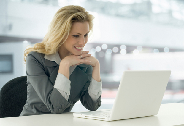 Image of lady looking at laptop screen and smiling