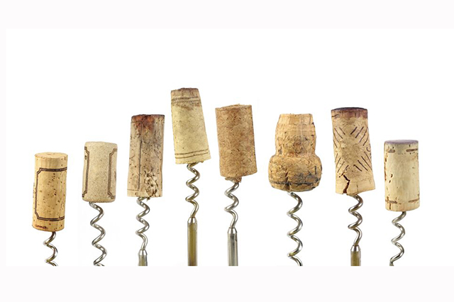 Image of  corkscrews in a row with corks on top of various size and shape